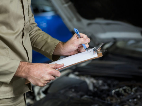 Mid-section of mechanic preparing a check list in repair garage