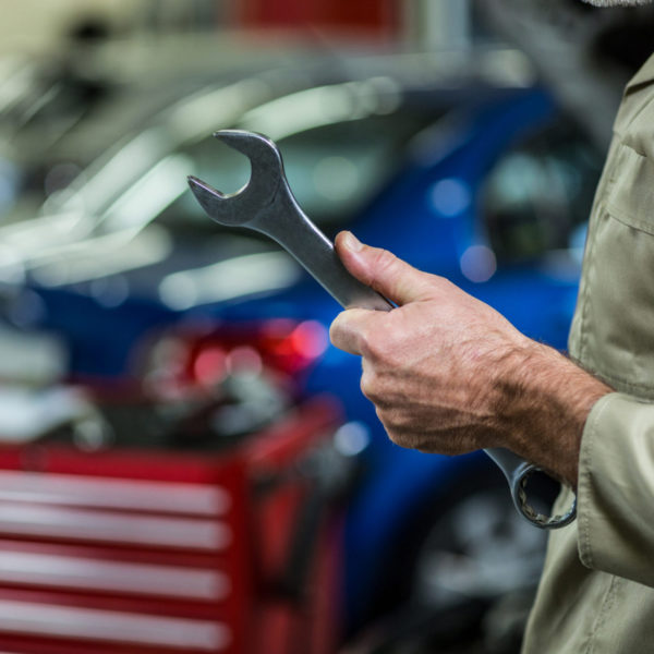 Mid-section of mechanic holding wrench tool in repair garage